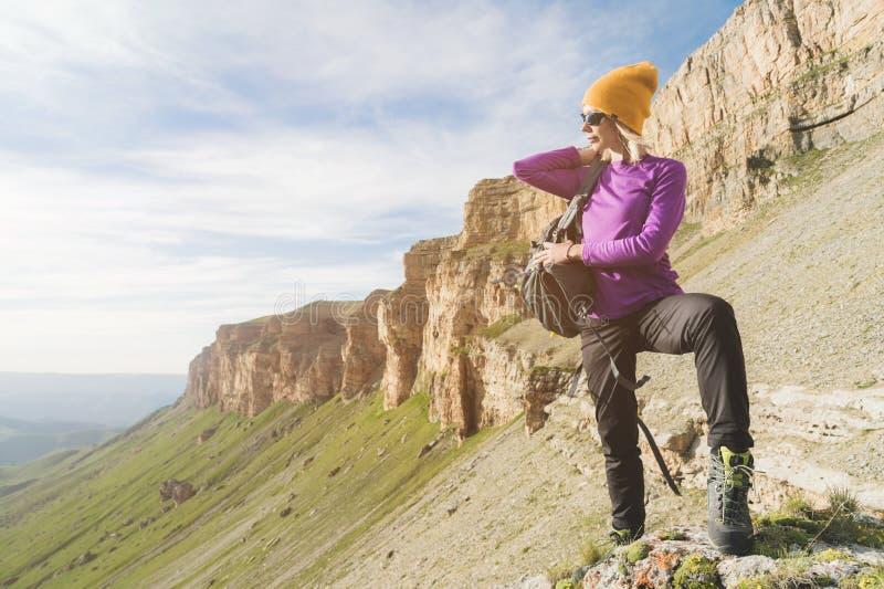 O turista da menina nos óculos de sol põe uma trouxa sobre a natureza em um fundo das rochas épicos que preparam-se para trekking fotos de stock