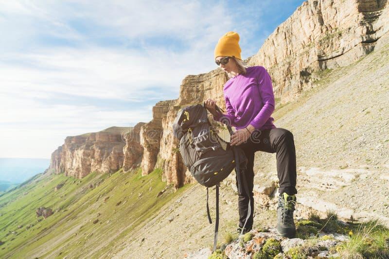 O turista da menina nos óculos de sol põe uma trouxa sobre a natureza em um fundo das rochas épicos que preparam-se para trekking imagem de stock royalty free