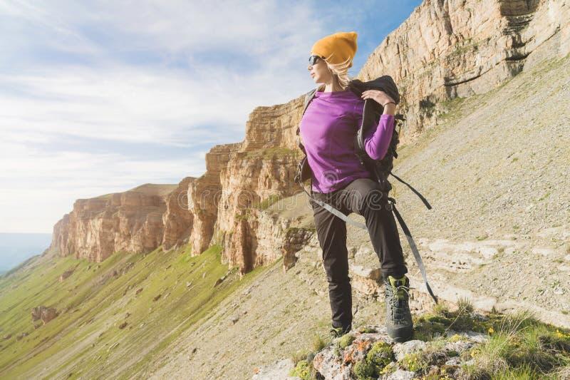 O turista da menina nos óculos de sol põe uma trouxa sobre a natureza em um fundo das rochas épicos que preparam-se para trekking foto de stock