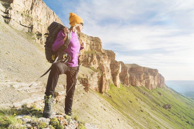 O turista da menina nos óculos de sol põe uma trouxa sobre a natureza em um fundo das rochas épicos que preparam-se para trekking imagens de stock