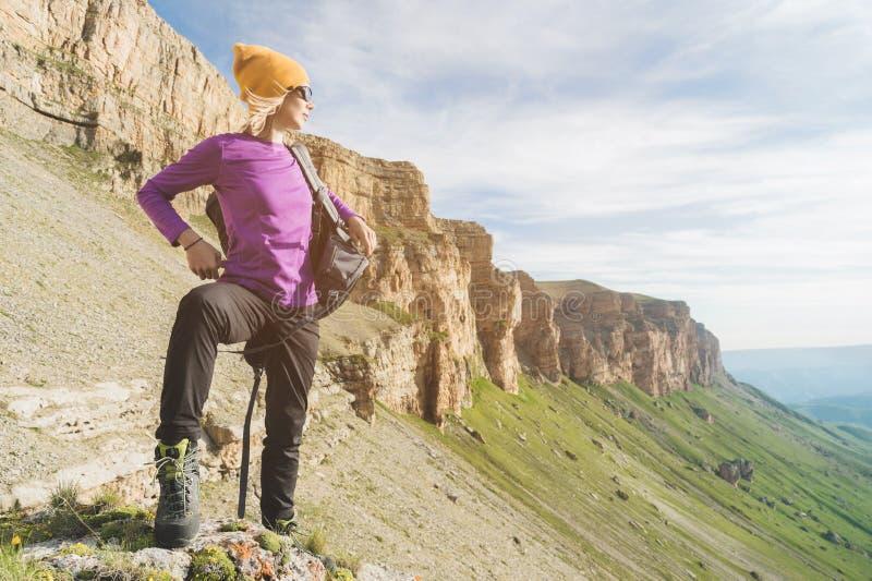 O turista da menina nos óculos de sol põe uma trouxa sobre a natureza em um fundo das rochas épicos que preparam-se para trekking imagens de stock royalty free
