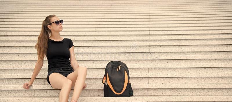 O turista da menina que relaxa em escadas rochosos aproxima sua trouxa Minuto da tomada a relaxar Equipamento preto ? moda dos ?c foto de stock