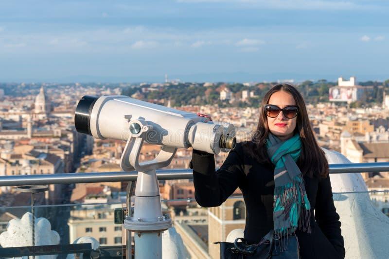 O turista da mulher está estando próximo aos binóculos na cidade Roma foto de stock