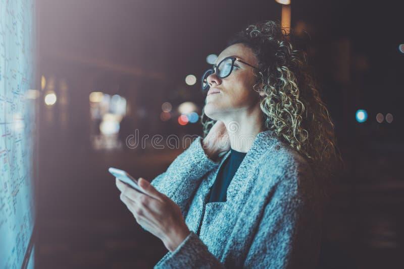 O turista encantador da mulher elegante com os vidros dos olhos que guardam o telefone celular entrega ao olhar o mapa da cidade  imagem de stock royalty free