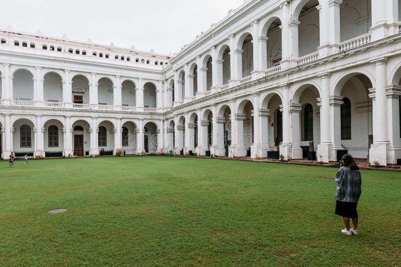 O turista está tomando uma foto do estilo arquitetónico vitoriano com o pátio do centro dentro do museu indiano imagem de stock