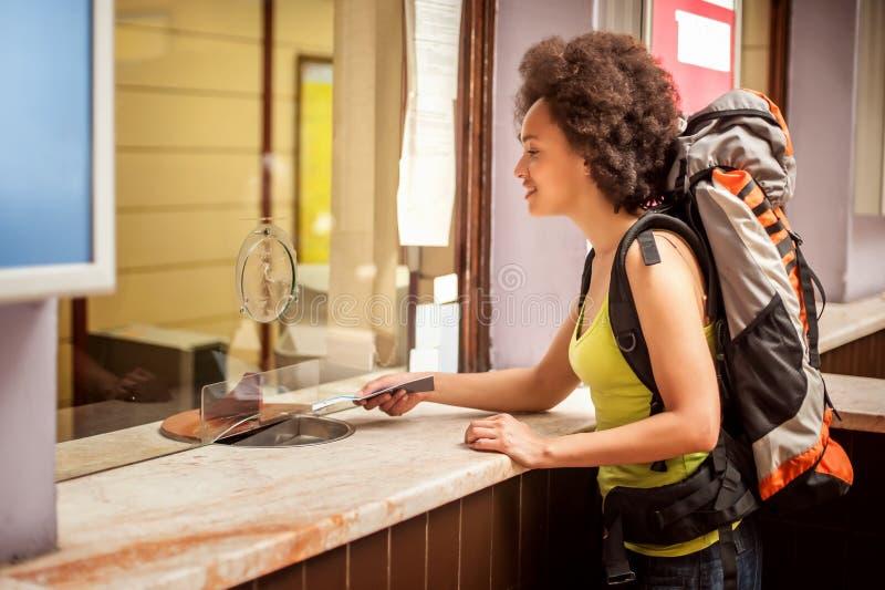 O turista fêmea compra um bilhete no contador de bilhete da estação terminal fotografia de stock