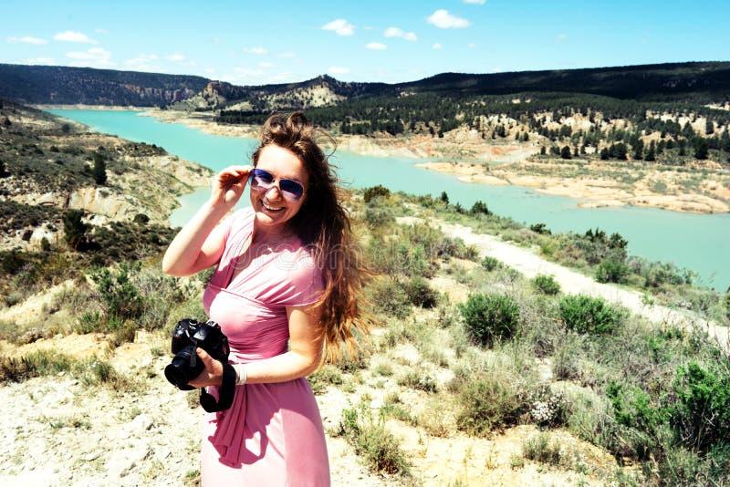 O turista fêmea de cabelos compridos em um vestido cor-de-rosa com uma câmera está nas montanhas foto de stock