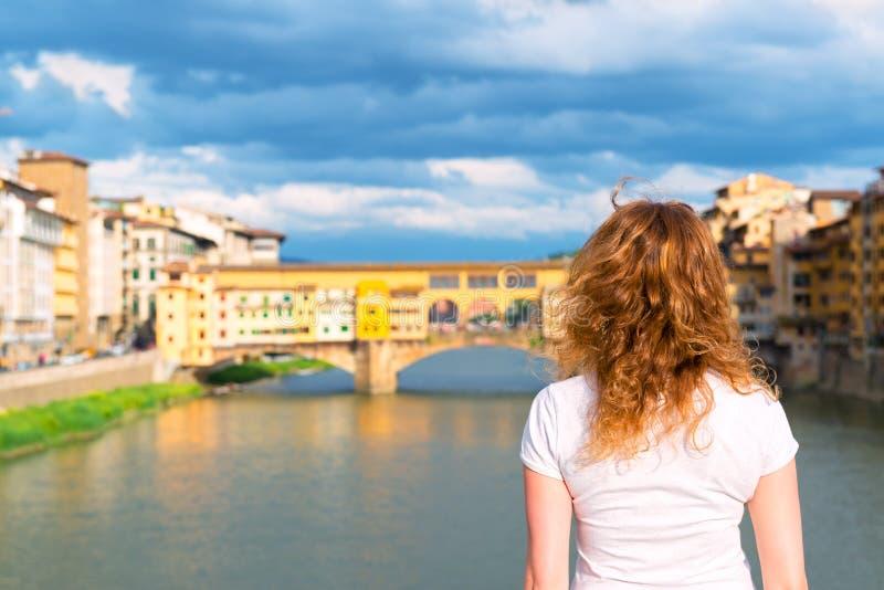 O turista fêmea novo olha o Ponte Vecchio em Florença fotos de stock royalty free