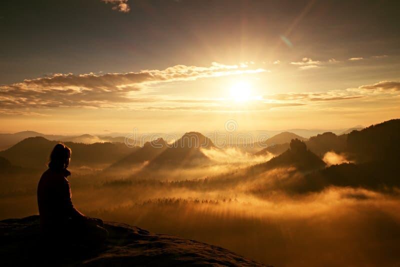 O turista longo novo bonito da menina do cabelo aprecia a aurora no canto afiado da rocha do arenito e olha-a sobre o vale a Sun imagens de stock