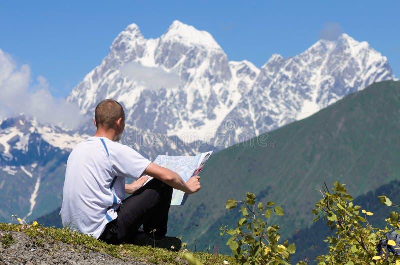 O turista nas montanhas olha o mapa fotografia de stock