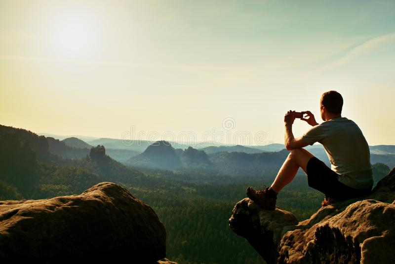O turista no t-shirt cinzento toma fotos com o telefone esperto no pico da rocha Paisagem montanhosa sonhadora abaixo, nascer do  fotos de stock