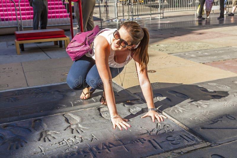 O turista põe a mão nos handprints da saga crepuscular protagoniza em Los Angeles fotografia de stock royalty free