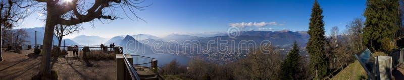 O turista que admira a cidade dos cumes, do lago lugano e da Lugano de uma vigia aponta na montagem Bre foto de stock royalty free
