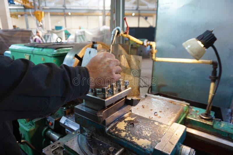 O Turner controla o processo do trabalho quando o produto é feito à máquina em um torno fotos de stock royalty free