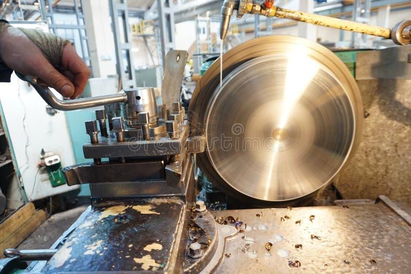 O Turner controla o processo do trabalho quando o produto é feito à máquina em um torno imagens de stock
