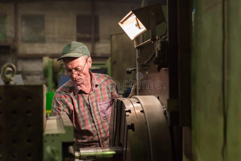 O Turner processa a peça de metal em um torno mecânico imagem de stock royalty free