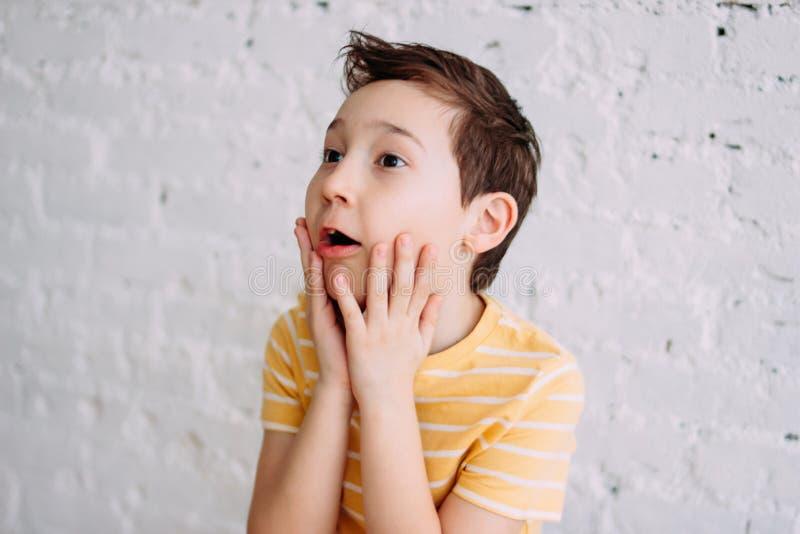 O tween bonito surpreendeu o menino com a cara engraçada no t-shirt amarelo isolado no fundo branco da parede de tijolo imagem de stock