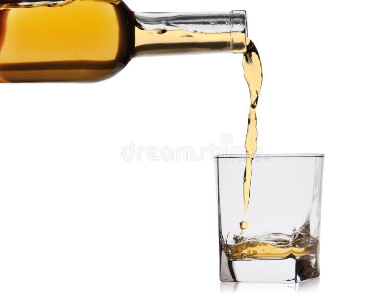 O uísque ou o conhaque derramaram em um vidro de uma garrafa isolada em um fundo branco fotografia de stock