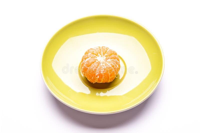 O um mandarino descascado em pires imagens de stock royalty free