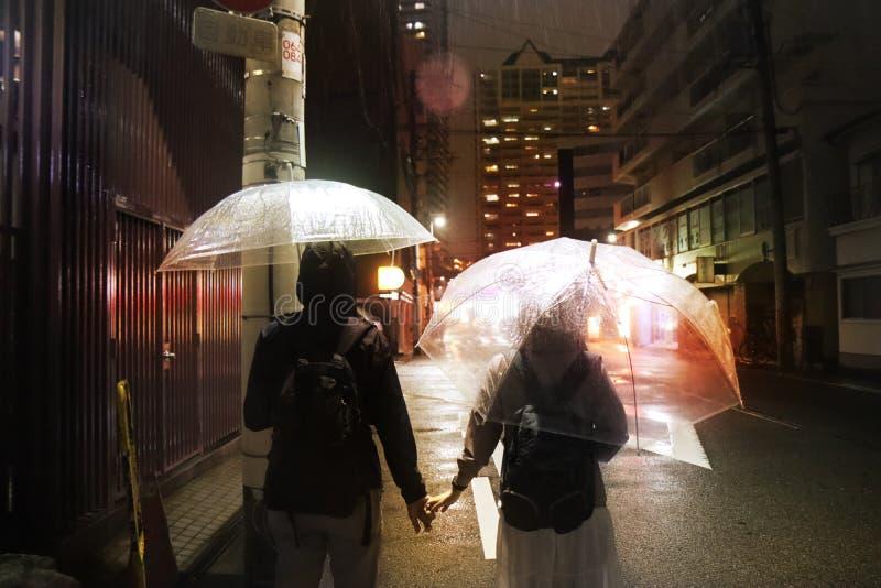 O umbralla transparente adolescente da posse do menino e da menina da trouxa anda em conjunto o streel do íon na noite chuvosa foto de stock royalty free