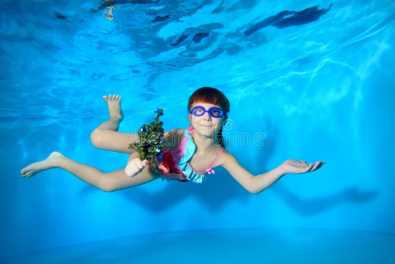 O Underwater na menina da piscina nada com um brinquedo à disposição, olhando a câmera e o sorriso imagem de stock royalty free