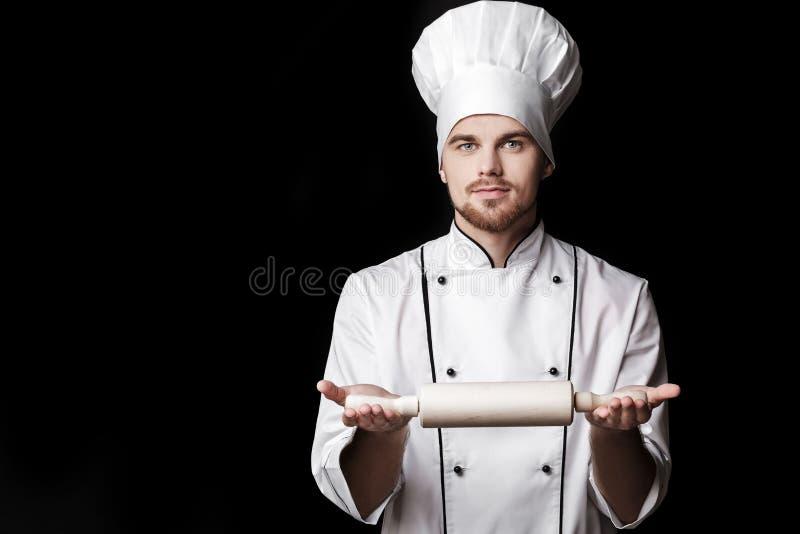 O uniforme branco de In do cozinheiro chefe farpado novo do homem guarda o pino do rolo no fundo preto imagens de stock