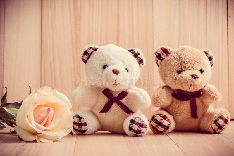 O urso dos pares senta-se perto da rosa da cor pastel, fundo de madeira foto de stock royalty free