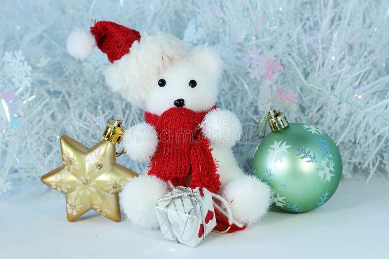O urso polar que veste um chapéu e um lenço vermelho levantou ao lado dos presentes connosco brilhantes em uma decoração do feria imagens de stock royalty free