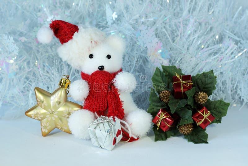 O urso polar que veste um chapéu e um lenço vermelho levantou ao lado dos presentes connosco brilhantes em uma decoração do feria fotos de stock
