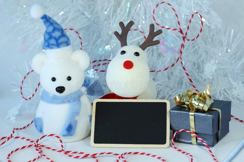 O urso polar que vestem um chapéu e um lenço azul para a decoração da festa de Natal com uma mensagem vazia slate imagem de stock royalty free