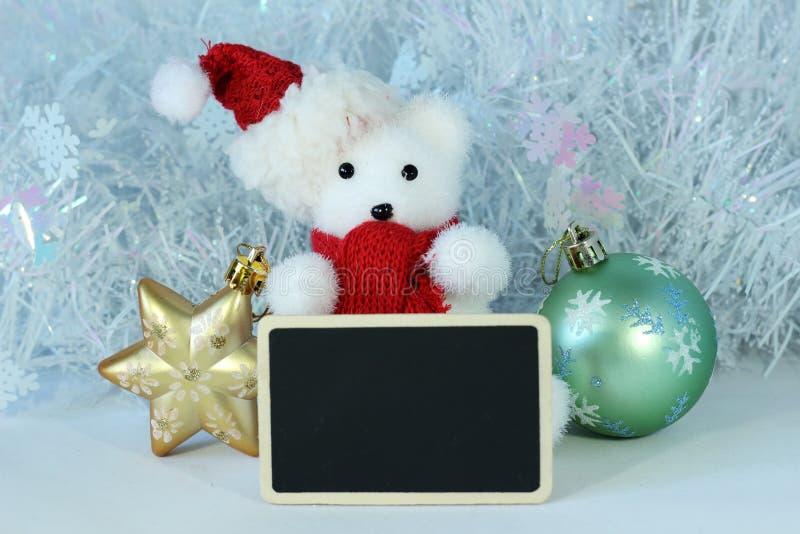 O urso polar que vestem um chapéu e um lenço vermelho para a decoração da festa de Natal com uma mensagem vazia slate imagens de stock royalty free