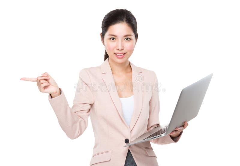 O uso da mulher de negócios do portátil e o dedo apontam de lado fotos de stock
