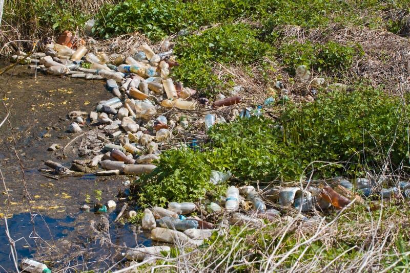 O vário lixo plástico das garrafas e os sacos poluem um rio pequeno fotos de stock