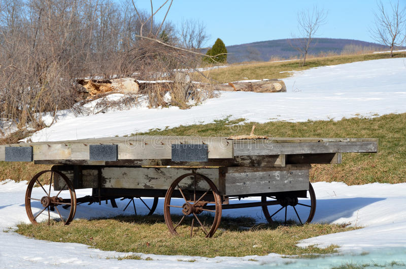 O vagão do suporte da exploração agrícola do vintage com aço roda dentro o inverno fotografia de stock royalty free