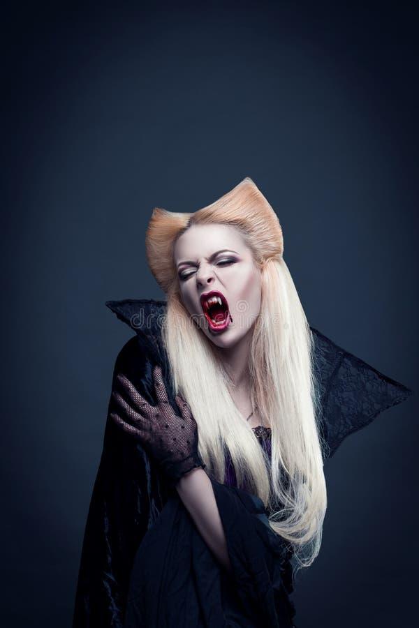 O vampiro louro bonito da menina com sangue está na boca imagem de stock royalty free
