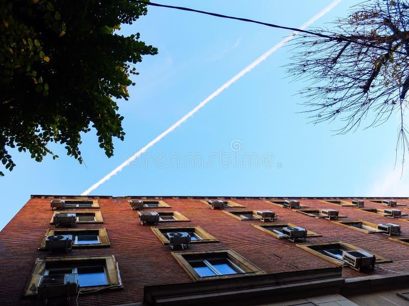 O vapor dos aviões de um fluxo plano no céu imagem de stock