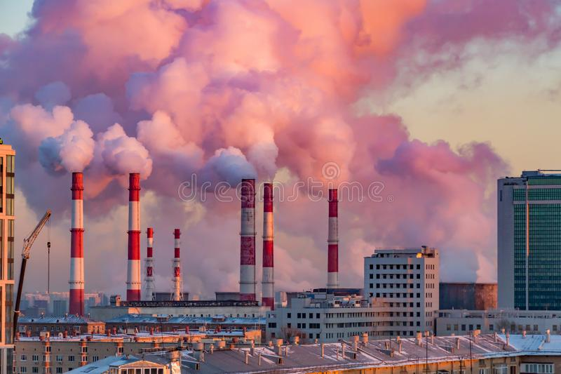 O vapor ou o fumo vêm das tubulações Calor combinado e central elétrica na cidade Paisagem no por do sol ou no alvorecer foto de stock royalty free