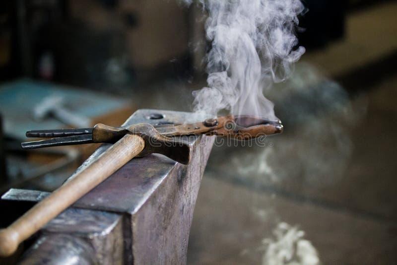O vapor vem das ferramentas e das mentiras diferentes do martelo no batente na forja fotografia de stock royalty free