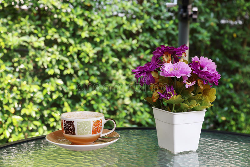 o vaso de flor e o copo de café na tabela de vidro com borrão esverdeiam o backgr foto de stock royalty free