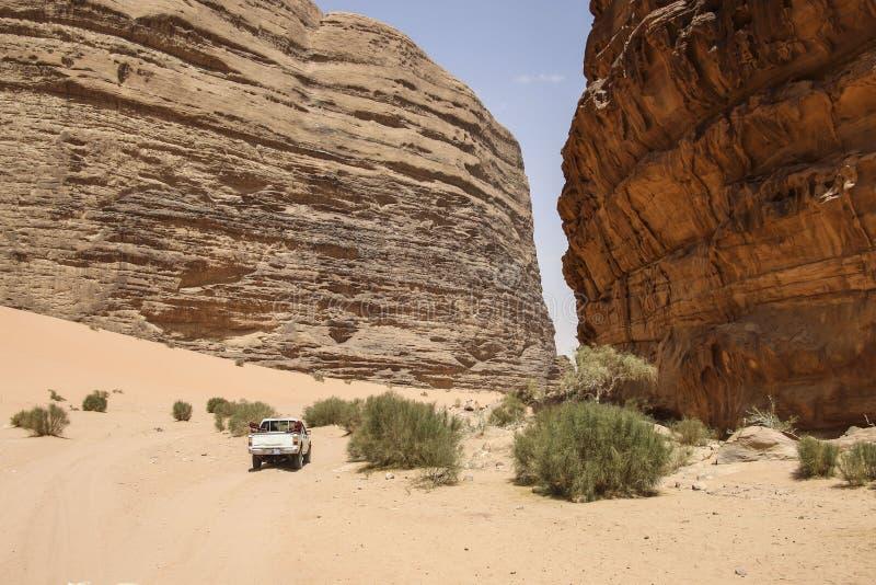 O veículo fora de estrada para safaris monta através das montanhas vermelhas de imagens de stock