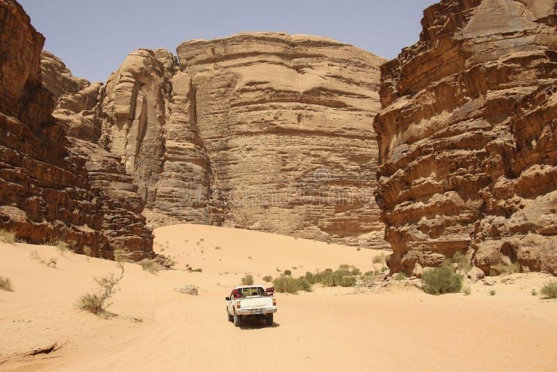 O veículo fora de estrada para safaris monta através das montanhas vermelhas da garganta do deserto de Wadi Rum em Jordânia Wadi  imagem de stock royalty free
