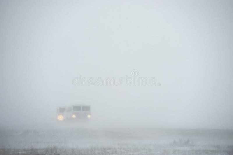 O veículo todo-terreno para a neve tropeça a um blizzard da neve na tundra Carro especial para o safari ártico imagens de stock royalty free