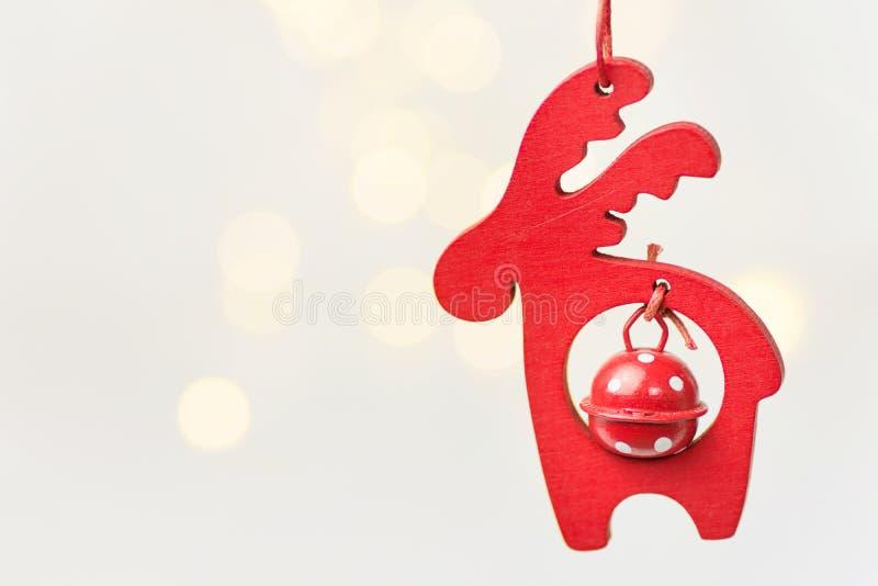 O veado vermelho de madeira do ornamento do Natal com o sino que pendura no fundo branco com bokeh dourado da festão ilumina-se fotos de stock