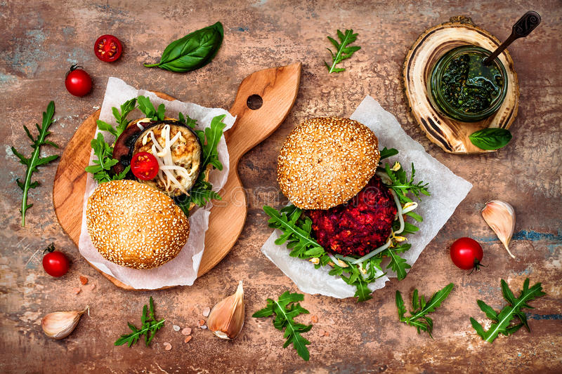 O vegetariano grelhou a beringela, a rúcula, os brotos e o hamburguer do molho do pesto Beterraba do vegetariano e hamburguer do  imagens de stock