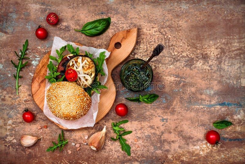 O vegetariano grelhou a beringela, a rúcula, os brotos e o hamburguer do pesto Beterraba do vegetariano e hamburguer do quinoa Vi fotos de stock