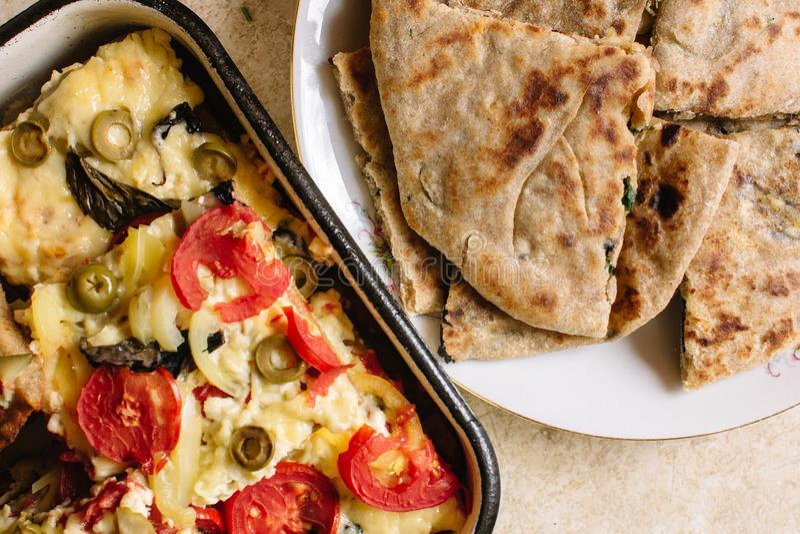 O vegetariano trata a pizza com os tomates, a mussarela e as azeitonas e o naan com queijo e verdes foto de stock royalty free