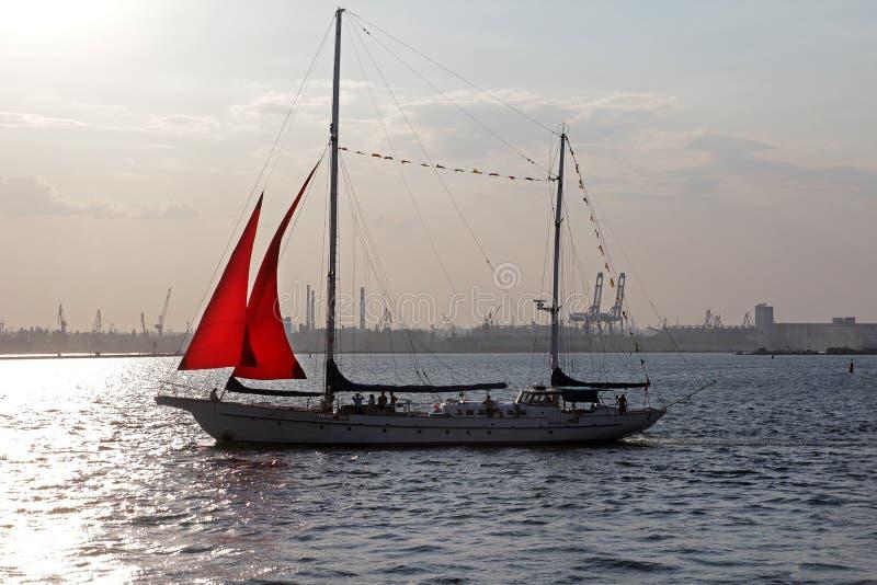 O veleiro com as velas vermelhas das velas no mar imagem de stock royalty free