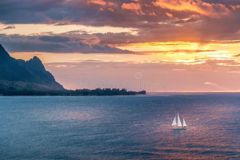 O veleiro cruza o por do sol na costa da ilha de Kauai imagens de stock