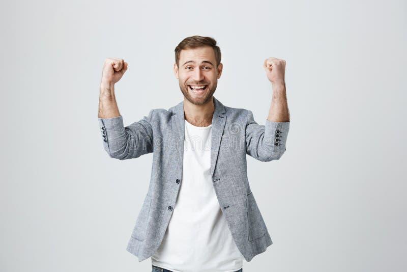 O vencedor masculino extático afortunado feliz com restolho na roupa na moda aperta os punhos, exulta o triunfo no trabalho, cont foto de stock