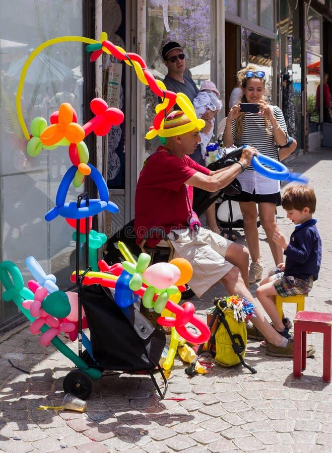 O vendedor ambulante de bolas infláveis faz para um menino uma coroa da bola na cidade de Tel Aviv em Israel fotografia de stock